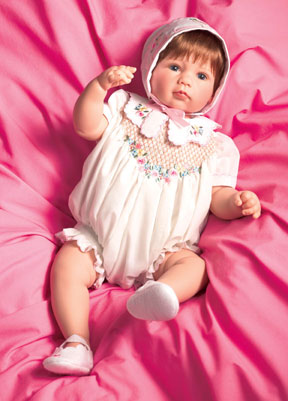 """Simple Treasures"" wears apparel designed by Martha Pullen. Her attire consists of a soft cotton romper, and features hand smocking trimmed with embroidery. Part of the Yesteryear Treasures series, the doll is attractively priced at $185."