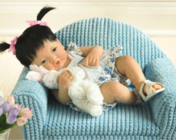 """Baby Lei takes her soft plush bunny with her wherever she goes. The 14-inch all-vinyl cutie's name means """"flower bud,"""" and she'll surely make your heart bloom."""