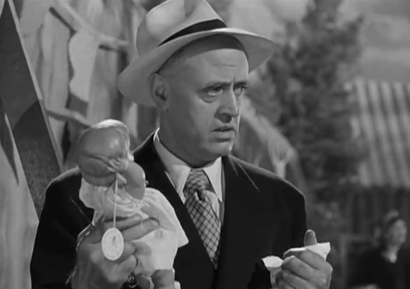 Alastair Sim as Commodore Gill, with the fatalistic baby doll
